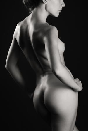 mujer desnuda de espalda: Mujer desnuda de pie de nuevo en una media vuelta. Su cuerpo es sexy es fotografiado en la oscuridad con algunos toques de luz. Foto de archivo