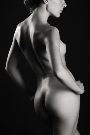 naked woman back: Nackte Frau steht wieder in einer halben Umdrehung. Ihr sexy K�rper wird im Dunkeln mit ein paar Highlights fotografiert.