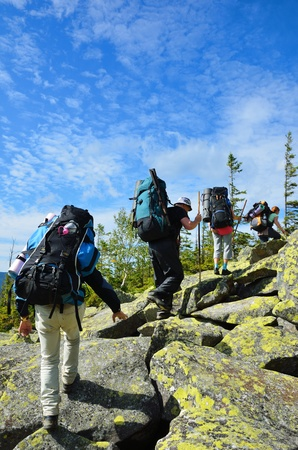 Group of tourists are climbing up the mountain. They are carrying the large rucksacks. Hikers are walking through the moraine.