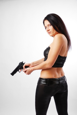 Serious woman is holding both hands a gun. She is turning around. Pretty girl is wearing a black leather top and tight pants.