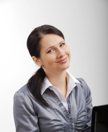 Happy businesswoman is working with a laptop  She is looking at the camera and smiling  Stok Fotoğraf