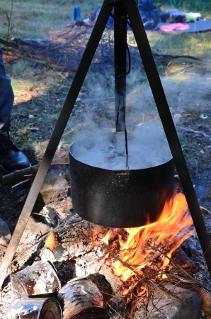 Blackened kettle with boiling soup is on the bonfire burning. It is hung on a metal tripod.