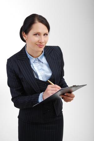 noting: Young office worker is standing and noting in the folder. The attentive woman is looking at the camera. She is wearing a dark business suit and a white blouse. Stock Photo