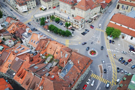 Fribourg is photographed from above. Its old city is one of the best maintained in Switzerland. There are red tile roofs, a town square, cosy streets, medieval townhouses tightly adjacent to each other. The molasse buildings are many storeys high.