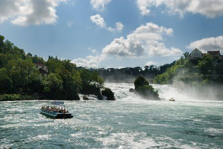 The Rhine Falls is the largest plain waterfall in Europe. A pleasure boat carries tourists close to the Rheinfall on the Upper Rhine in northern Switzerland.