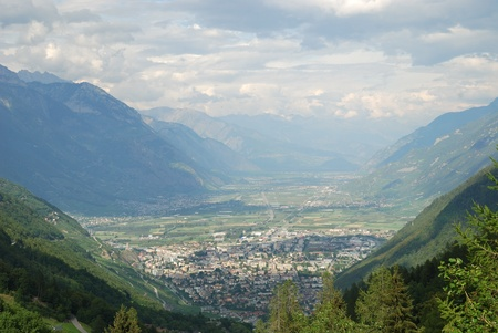 The small town of Martigny is located on the Rhone elbow in the Swiss Alps  It is surrounded by vineyards and orchards