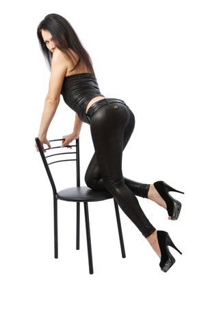 Sexy woman leans on the black chair. She is looking at the camera. Pretty girl is wearing a black leather top, tight pants and high-heeled shoes.