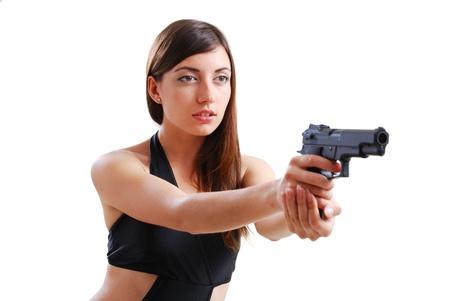 Pretty woman is aiming a handgun. She is holding a gun both hands. photo