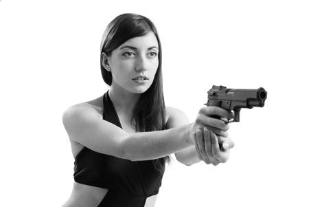 A nice woman is aiming a handgun. She is holding a gun both hands. photo