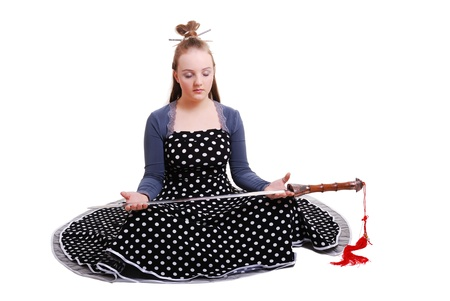 animation teenagers: Serious teenage girl is sitting and holding a sword in front of herself. Her eyes are closed. She is wearing an anime costume.