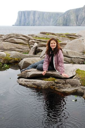 Cheerful woman is sitting near the small lake is in the middle of the stones. There is a dark cliff in the background. This is the most northern cape of Europe in the Barents Sea. photo