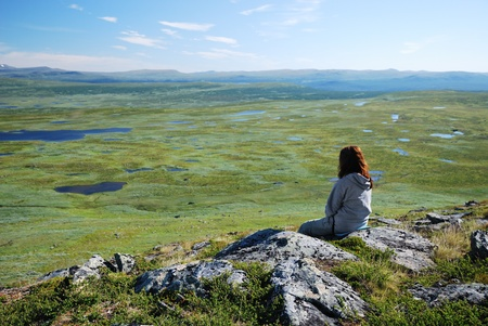 tableland: A woman is sitting on the top of the hill in Swedish Lapland. There are a lot of small lakes on the green tableland reaching to horizon. Vindelfjallen�s nature reserve is photographed in summer.
