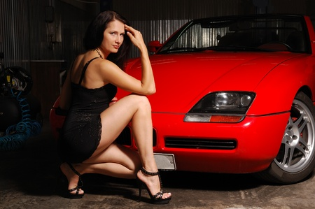 A sexy driver is squatting in front of the red sport car. The photo is made in a garage. Young woman is wearing a short black dress and high heels. photo