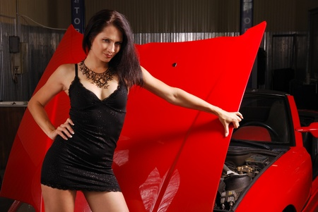 A sexy driver is standing and holding by the lifted bonnet of the red sport car. Young woman is wearing a short black dress. photo
