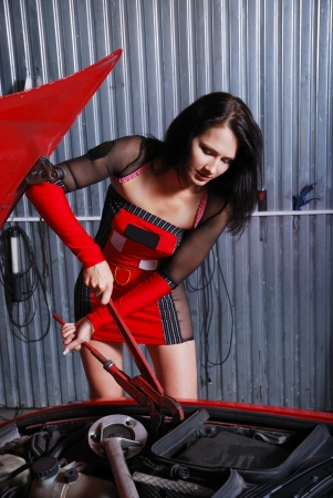 bonnet: A sexy girl is fixing something under the hood in the garage. She is repairing her car by the screw wrench. Young woman is wearing a short dress with transparent insets.