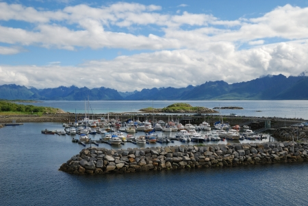 Various boats, yachts and motorboats are moored at the pier fenced round in the fjord. In the background there are majestic mountains. Stock Photo - 13841590