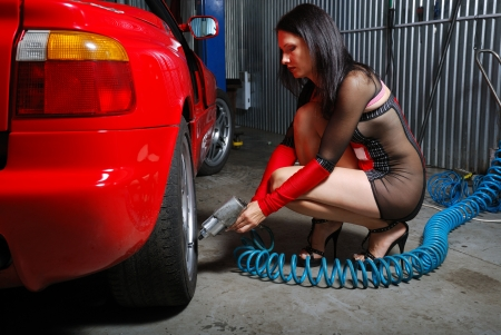 A sexy girl is inflating a tyre by the air pump. She is sitting near the red car in the garage. Young woman is wearing a short dress with transparent insets. Stock Photo - 13877052