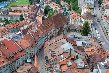 Fribourg is photographed from above. Its old city is one of the best maintained in Switzerland. There are red tile roofs, dense building up, medieval townhouses tightly adjacent to each other.  photo