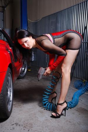 굽힘: 섹시한 여자는 차고에 빨간 차 근처에 몸을 굽히는입니다. 그녀는 두 손에 공기 펌프를 잡고있다. 젊은 여자는 투명 인 세트와 짧은 드레스를 입고있다.