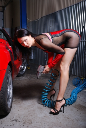 A sexy girl is is stooping near the red car in the garage. She is holding the air pump in both hands. Young woman is wearing a short dress with transparent insets. photo