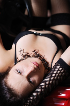A young woman is lying in the red sport car  She is wearing black lingerie, fishnet gloves and stockings  photo