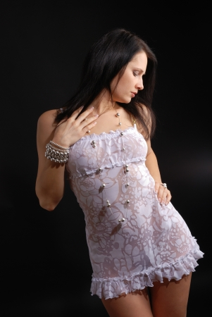 A young woman is standing and looking down. The sexy girl is wearing a short transparent dress with floral pattern, shiny beads and bracelets. Stok Fotoğraf