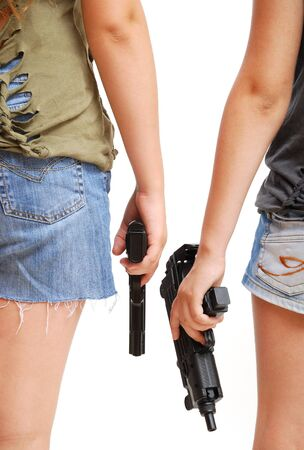 Two teenage girls are holding handguns. They are standing back side by side. Only her arms and halves of the body are in sight. They are wearing in shorts and t-shirts. photo