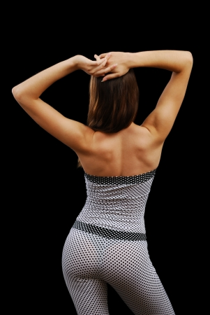 Young woman is bending her attractive body and putting her hands behind her head. She is wearing a polka-dot body suit. photo