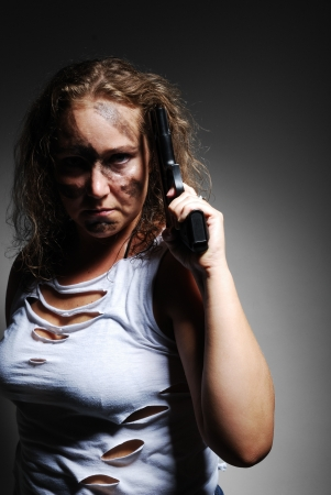 disguised: Severe woman is holding a gun near her temple and looking at the camera. Her face is disguised. She is wearing a rent T-shirt and torn jeans.