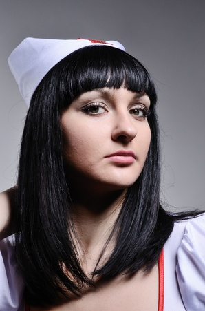 Pretty medical nurse is looking intently at the camera. She is wearing a white dress and a cap with red cross. photo