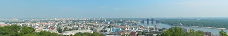 Kyiv is photographed in summer  In the right bank of the river Dnipro there is the old borough Podol with a port and bridges  In the background there is the skyline of residential district Obolong
