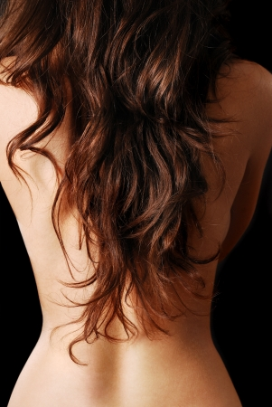 naked girl body: Nude female back is covered with dark tresses on the black background.