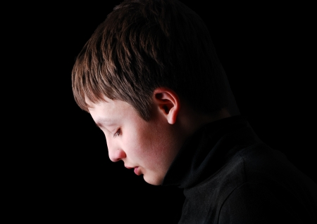 Teenage boy is photographed in profile on the black background. He is upset and his head are hung. She is wearing in black.