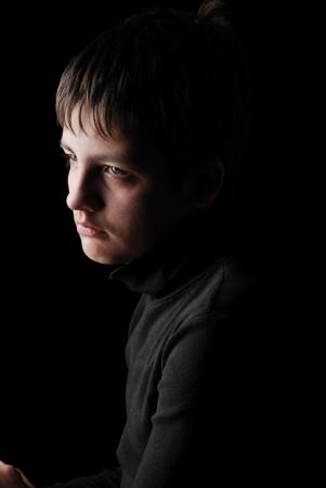 悲しい 10 代の少年は、黒の背景に撮影されます。彼は動揺です。彼女は黒を着ています。
