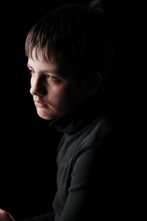 Sad teenage boy is photographed on the black background. He is upset. She is wearing in black.