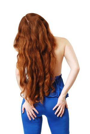 Red-haired woman is standing back with flowing hair  She put both hands on her buttocks  Her long red hair are curled