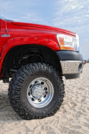 A front part of the off-road vehicle is photographed closeup in the dunes