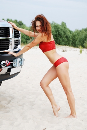 A sexy girl is pushing the bumper of the off-road vehicle in the dunes  Young woman is wearing a red top and shorts  photo