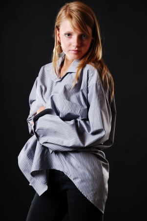 Young woman wraps herself in the large male shirt. She is looking at the camera with great attention. Stock Photo - 15812066