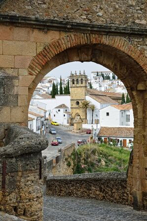 Ronda is the most well-known of white towns on the south coast of Spain. It is photographed through the stone arch of the ancient Arab bridge (Puente Viejo). photo