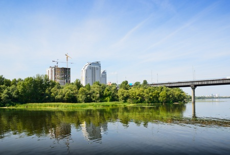riverside trees: Newly-erected building is on the riverside overgrown with trees and bushes. Stock Photo