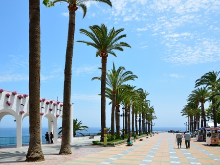 The square is in front of the Balcony of Europe in sunny day. There are a white stone portico with flowers, high palm trees and persons walking in Nerja on the Costa del Sol.