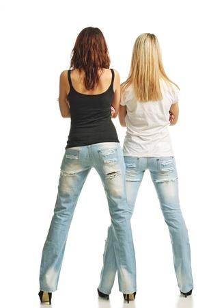 탱크 탑: 두 젊은 여성이 자신의 다리가 그들은 청바지, 탱크 탑 T-셔츠를 입고 있습니다 높은 발 뒤꿈치에 떨어져 심어 져 다시 서 스톡 사진