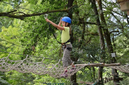 Preteen girl is climbing on the rope net at the ropes course    Standard-Bild