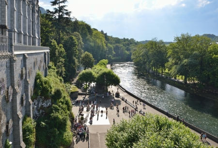 Lourdes is a major place of Roman Catholic pilgrimage  The Basilica of Our Lady of the Immaculate Conception  Upper church  is built on the top of the rock above the Grotto near the fast-flowing river Gave de Pau   Standard-Bild