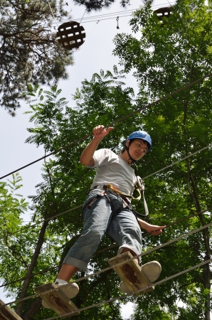 A teenage boy is moving up on the rope ladder.