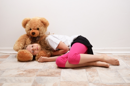 A blonde girl is lying on the floor. She is putting her head on the big teddy bear and looking at the camera.