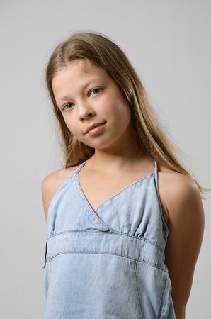 A preteen girl is standing and looking at the camera. Her fair long hair are flowing. She is wearing a jean sundress. Her arms are hid behind her back. photo