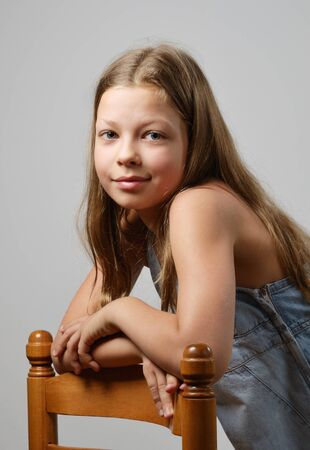 preteen girl: A preteen girl is smiling and looking at the camera. Her fair long hair are flowing. She is leaning on the back of chair.