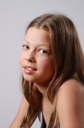 A pre-teen girl is photographed on the gray background